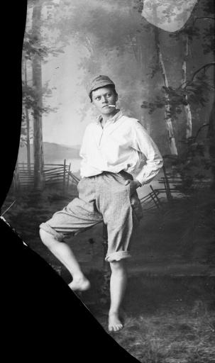 Marie Høeg i oppbrettede bukser, sixpence og sigarett i munnen.